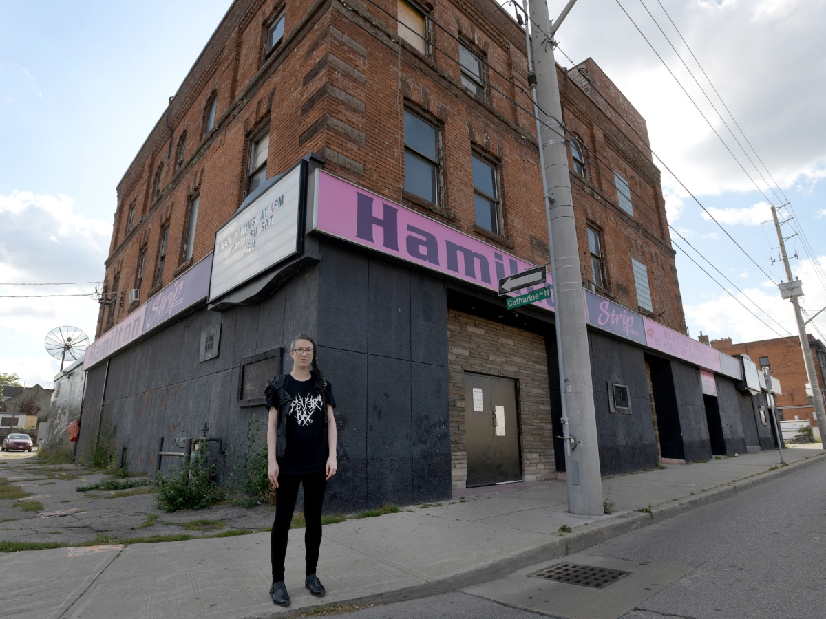 Hamilton, Ontario - September 24,2019- Sarah Sheehan, with a PhD in medieval Irish literature, arrived from Toronto a couple of years ago. She and her wife like Hamilton's built heritage and bought an old house near Barton and Victoria. Sarah often takes the Barton bus past the old three-storey Hanrahan's Hotel, a strip joint in more recent times. When she read last month that it had closed and was slated to be torn down, she started researching the building and its stories. She wonders if it just might be Hamilton's oldest purpose-built hotel in continuous use. She thinks the building deserves adaptive re-use, not demolition. Cathie Coward/ Hamilton Spectator